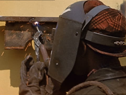 1945 close up welder using blow torch / lifting mask to reveal woman's face - costruttore navale video stock e b–roll