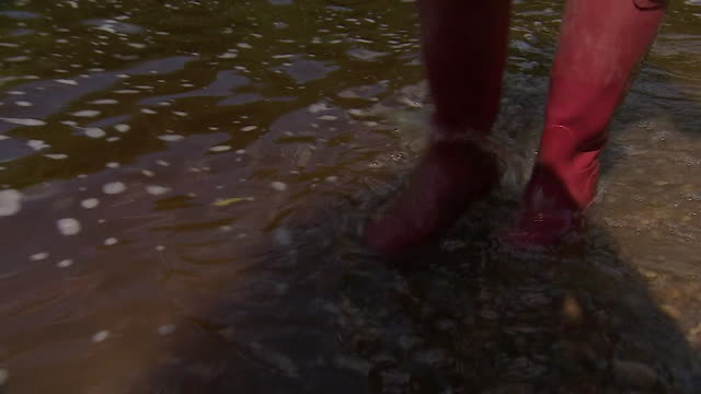 close up welly boots paddling through river ilkley - rowing stock videos & royalty-free footage