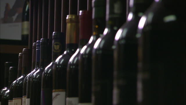 close up wide shot bottles standing on rack of wine cellar focus pull close up row of red wine bottles / pan red wine cellar - wine cellar stock videos and b-roll footage