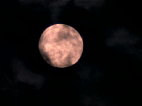 close up wispy grey clouds moving in front of full moon - wispy stock videos & royalty-free footage