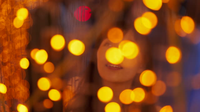 Close up, woman admires bright yellow lights
