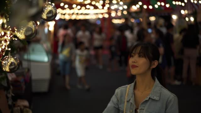 vídeos de stock, filmes e b-roll de close up, woman admires lights in chiang mai shopping center - só uma mulher de idade mediana