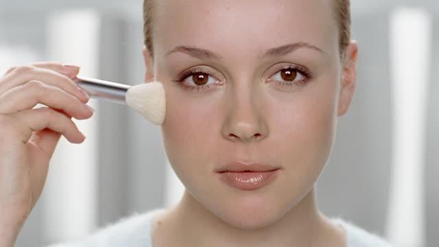 vídeos de stock, filmes e b-roll de close up woman applying blush with brush / looking at cam - blush
