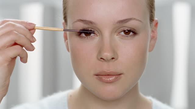 Close up woman applying mascara / looking at CAM
