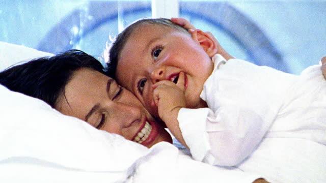 vídeos de stock, filmes e b-roll de close up woman + baby cuddling / baby smiling - superexposto