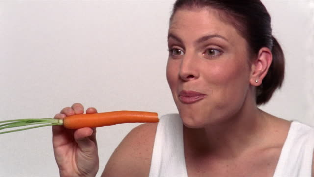 close up woman biting into carrot and smiling - möhre stock-videos und b-roll-filmmaterial