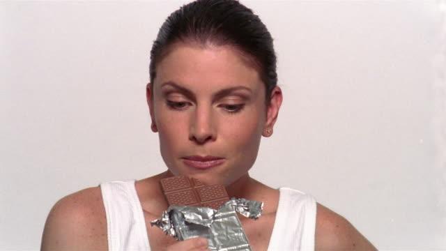 Close up woman biting into chocolate bar and smiling at camera