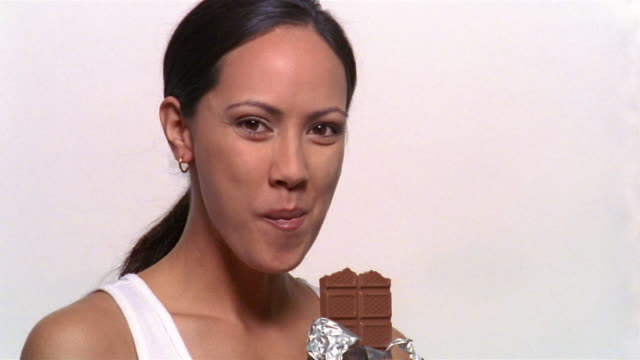 close up woman biting into chocolate bar and smiling at camera - tasting stock videos and b-roll footage