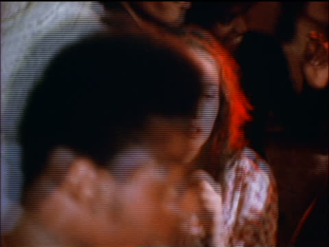 1974 close up woman dancing with Black man in hat at party indoors / documentary