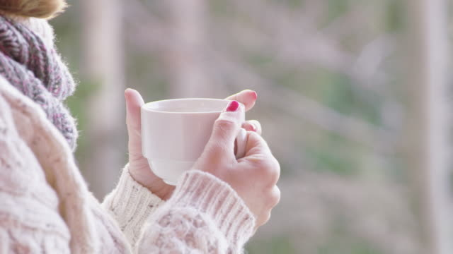 4k close up woman drinking hot, steaming tea on winter patio, slow motion - tea hot drink stock videos & royalty-free footage