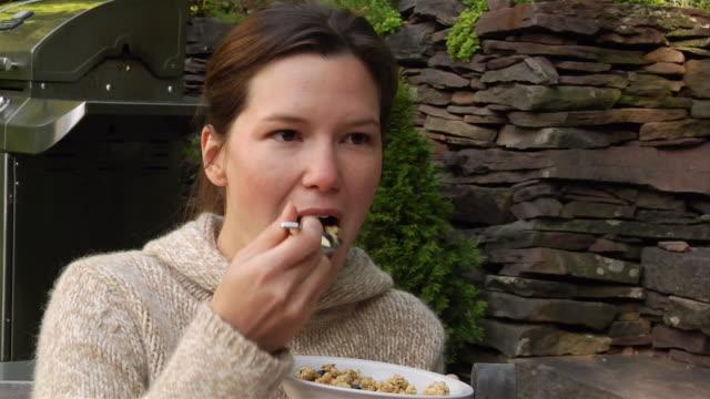 Close up woman eating bowl of granola outdoors