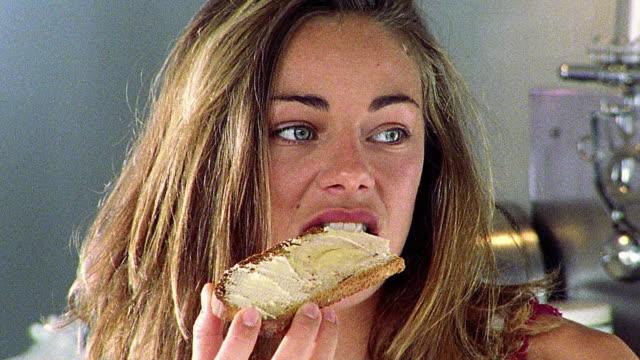 vidéos et rushes de close up woman eating bread in kitchen - pain