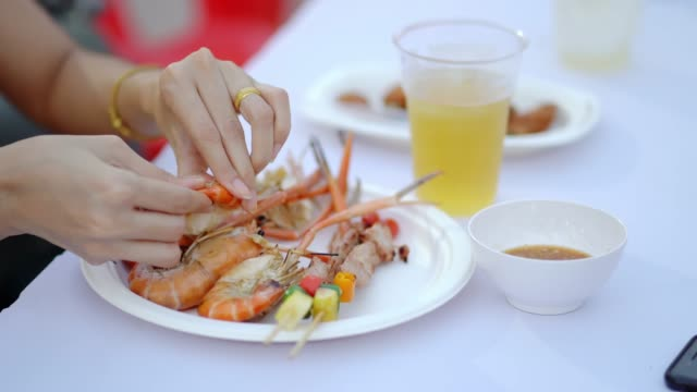 close up, woman eating shrimp with barbecue on plate and drink beer in party. - prawn stock videos & royalty-free footage