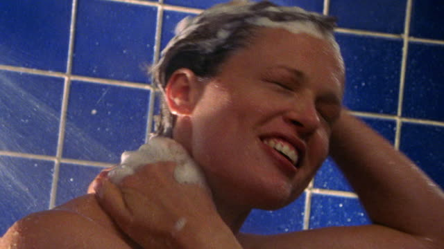 close up woman enjoying washing her hair in shower - shampoo per capelli video stock e b–roll