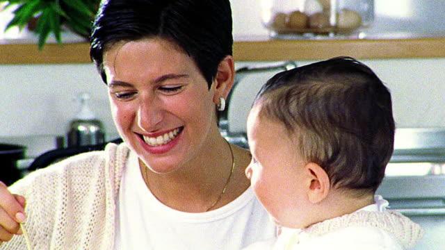vídeos de stock, filmes e b-roll de close up woman feeding child baby food - superexposto