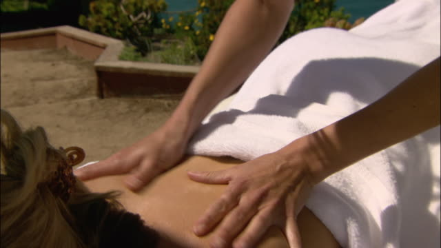 vídeos de stock e filmes b-roll de close up woman getting massage/ zoom out masseuse with coastline in background/ monterey county, california - mesa de massagem