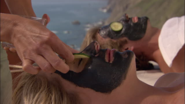 vídeos de stock, filmes e b-roll de close up woman giving couple mud masks with ocean in background/ monterey county, california - mesa de massagem