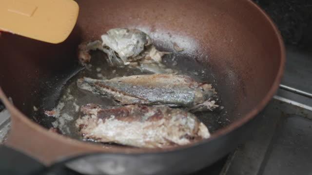 nahaufnahme: frau hand pfanne fisch auf pfanne. - skillet cooking pan stock-videos und b-roll-filmmaterial