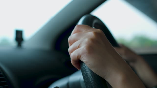 close up woman hand holding control wheel driving on road in sunny day - learning to drive stock videos & royalty-free footage