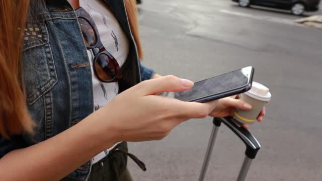 chiudi la mano della donna ordina un taxi dalla sua applicazione smartphone mobile mentre si trova sul marciapiede - taxi video stock e b–roll