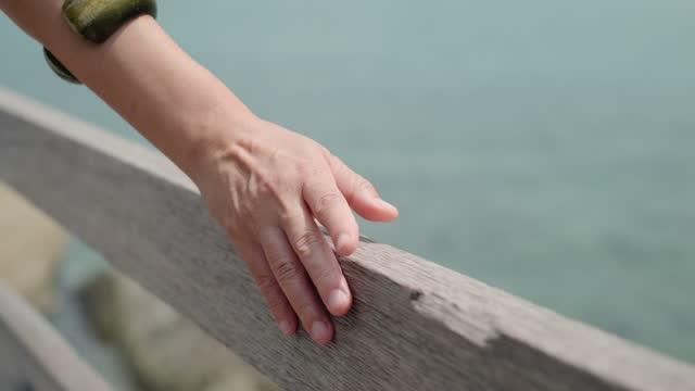 närbild kvinna hand röra och glida över träbro handräcke till sjöss på sommarsemester - railings bildbanksvideor och videomaterial från bakom kulisserna
