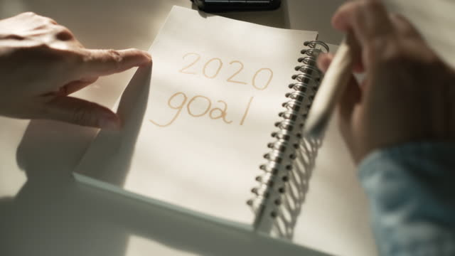 close up woman hand writing 2020 new year goals on notebook on desk with morning sunlight from window - 2020 business stock videos and b-roll footage