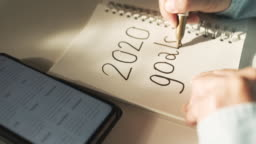 Close up woman hand writing 2020 new year goals on notebook on desk with morning sunlight from window