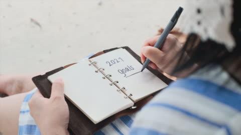 夏休み時間にビーチに座って2021年の目標を書く女性の手書きを閉じる - aspirations点の映像素材/bロール