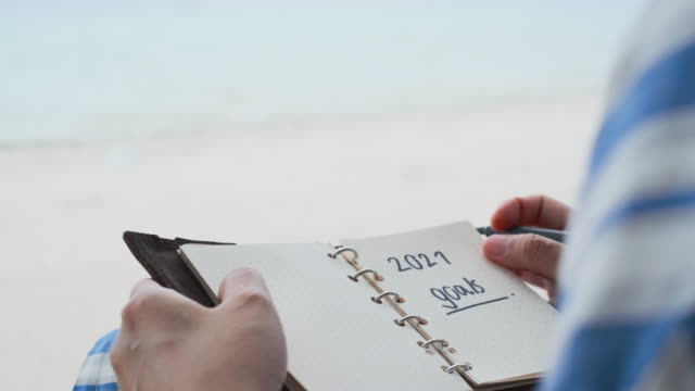close up woman hand writing 2021 goals sitting at beach on summer vacation time - aspirations stock videos & royalty-free footage