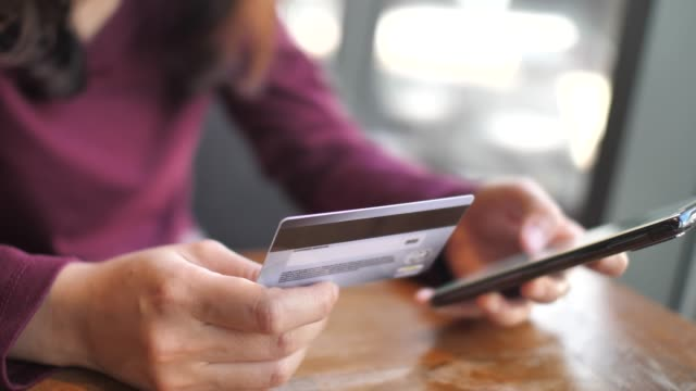 close up woman hands using mobile smart phone and holding credit card - credit card stock videos and b-roll footage