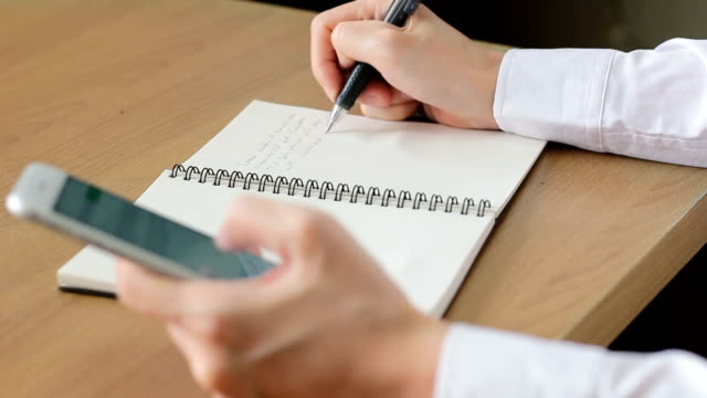 Close up woman hands writing on notebook with using smartphone
