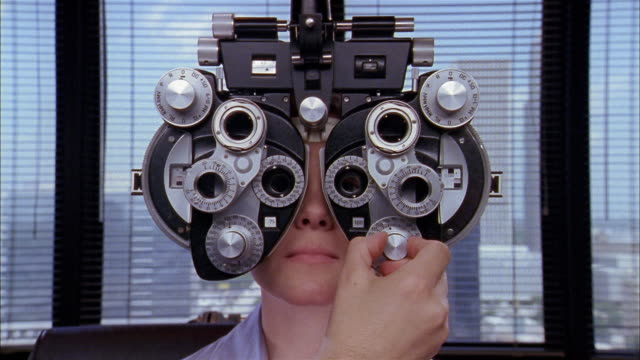 close up woman having eyes examined / man's hand turning knobs and adjusting machine - optical instrument stock videos & royalty-free footage