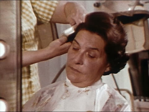 1968 close up woman having her hair styled at a salon / zoom out another woman having hair set / audio - human head stock videos & royalty-free footage