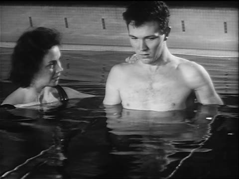 B/W 1958 close up woman helping disabled man walk in pool in physical therapy