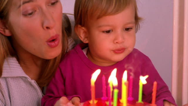 close up woman helping girl toddler blow out candles on birthday cake / toddler clapping