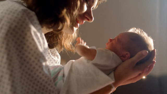 Close up woman holding and talking to crying newborn baby
