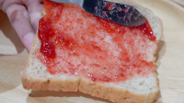 close up, woman holding knife spreading jam strawberry on bread. - toasted bread stock videos & royalty-free footage
