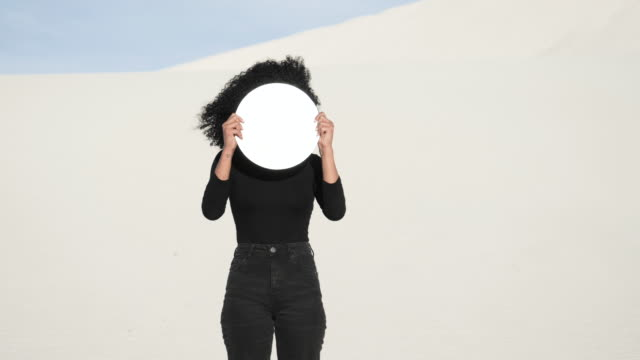 vidéos et rushes de close up, woman holds reflective circle in desert - visage caché