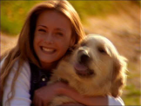 close up woman hugging dog + smiling at camera