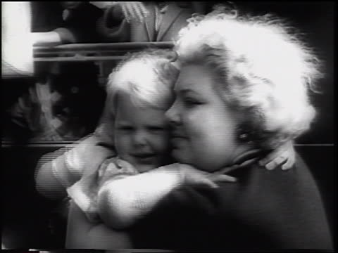 b/w 1961 close up woman hugging small boy outdoors / east german refugees / beginning of berlin wall - 1961 stock-videos und b-roll-filmmaterial