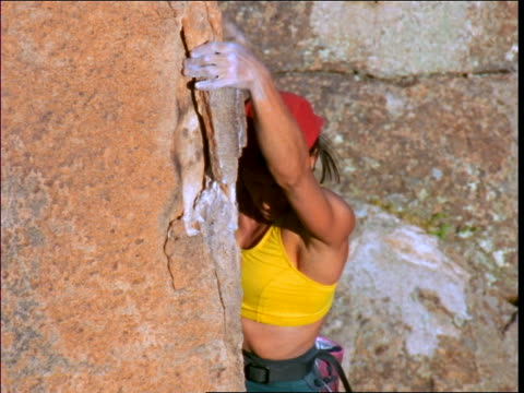 vídeos y material grabado en eventos de stock de close up woman in baseball cap climbing up rock face - 1997