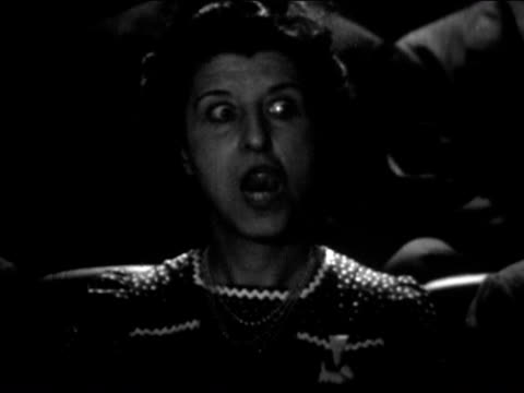 1941 close up woman in cinema with wide eyes rubbing tongue around mouth and over teeth - biosalong bildbanksvideor och videomaterial från bakom kulisserna