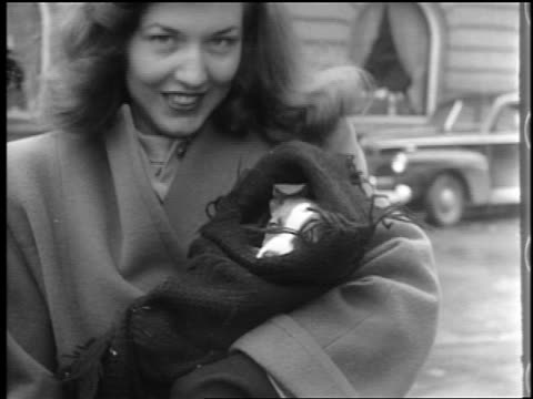 B/W 1944 close up woman in coat holding small dog wrapped in blanket outdoors / Lexington, NC / docu.