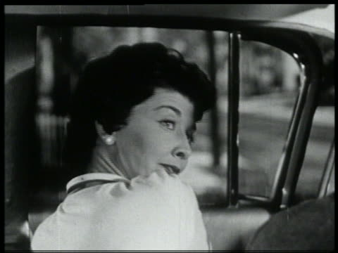 b/w 1959 close up woman in drivers seat looking over her shoulder - 1959 stock-videos und b-roll-filmmaterial