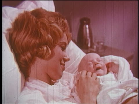 1960 close up woman in hospital bed holding screaming newborn baby + smiling