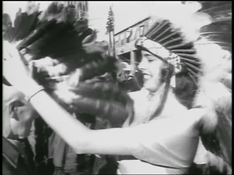 vídeos de stock e filmes b-roll de b/w 1954 close up woman in native american headdress puts headdress on kisses returning soldier - 1954