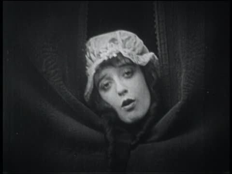 b/w 1916 close up woman in nightcap poking head thru curtains + puckering lips - 1916 stock videos & royalty-free footage