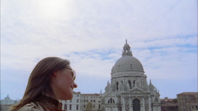 Close up woman in sunglasses smiling on balcony w/cathedral dome in background / Venice, Italy