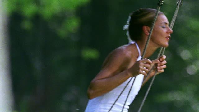 stockvideo's en b-roll-footage met close up pan woman in white dress swinging on tree swing outdoors - witte jurk