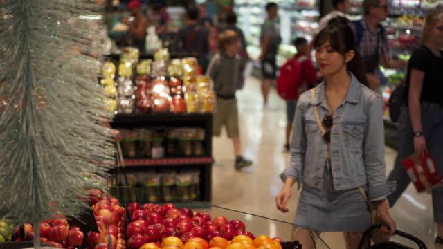 vídeos de stock, filmes e b-roll de close up, woman inspects produce in grocery store - jaqueta jeans